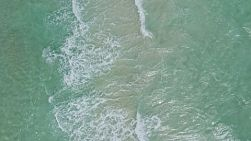 Bird's eye view of waves washing ashore on a windy day in Perth, Western Australia.