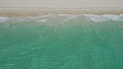 Bird's eye view of waves washing onto a sandy beach in Perth, Western Australia.