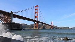 Waves pound the coastline hard under the famous Golden Gate bridge on a gorgeous sunny day in San Francisco, California.