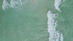 Bird's eye view from a drone of waves washing ashore on a windy day in Perth, Western Australia.