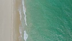 Bird's eye view of waves washing onto the shore on a windy day, onto a sandy beach in Perth, Western Australia.