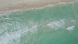 Drone shot of waves washing ashore on a windy day in Perth, Western Australia, with the shot rotating.