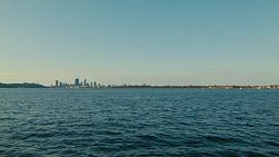 A wide angle view of the Swan River, with the Perth City skyline on the horizon.