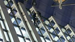 Two Asian window washers washing windows at an airport in Shanghai, China at lightning speed.