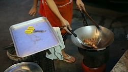 A Thai lady cooks chicken in hot oil in her wok on the streets of Bangkok, Thailand.