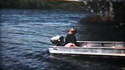 A beautiful red headed woman with cat glasses takes a motorboat out for a drive on a peaceful lake.