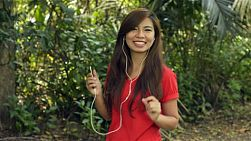 Young asian woman dancing to music on her headphones, turns and smiles at the camera.