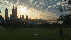 A woman drinking water from a bottle as she sits on the grass in King's Park, watching the sun rise over the Perth City skyline in Western Australia.