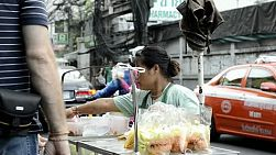 A woman cutting up and bagging fruit from her vendor cart in Bangkok, Thailand.