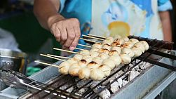 A woman cooking delicious pork balls on an open grill on the streets of Bangkok, Thailand.