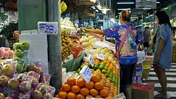 A Thai woman weighing bags of grapes at a fresh fruit market in Bangkok, Thailand. dolly / tracking shot.