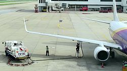 Men refueling a plane at Don Muang Airport, Bangkok, Thailand.