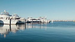 Blue skies over rows of yachts and boats berthed in the blue waters of Fremantle Fishing Boat Harbour in Western Australia.