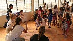 A group of young adults on a short-term overseas mission trip have fun teaching action songs to Khmer children in the slums of Phnom Penh, Cambodia.