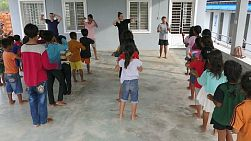 A group of young adults on a short-term overseas mission trip have fun teaching action songs to Khmer children in rural Cambodia.