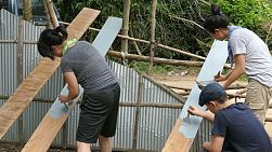 A group of young adults on a short-term overseas mission trip work hard building a new home for a needy family in rural Cambodia.