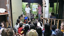 A group of young adults on a short-term overseas mission trip share a bible story with the kids living in the slums of Cambodia.