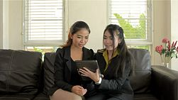 Two young asian women showing and discussing work on their tablet computer.