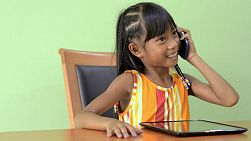 A young Asian girl is interrupted while using a tablet computer by a phone call, she answers the mobile phone and has a happy conversation.