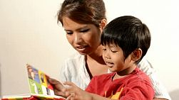 Young Asian woman reading a book together with a young boy.