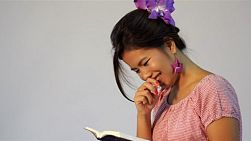 Young Asian woman bursts out laughing as she reads a book or the bible.