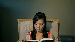 Young asian woman relaxing on a chair, reading the bible/ a book - tracking into focus.