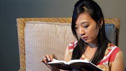 Young Asian woman relaxing on a chair, reading the bible or a book.