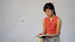 Young Asian woman thinking while reading a book or the bible - dolly tracking shot.