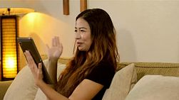 A beautiful asian chatting to a friend on her tablet computer in the comfort of her home.