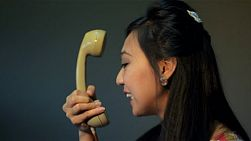 Vintage dressed young asian woman having an argument on the phone and screams into the phone - tracking shot.