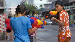Bangkok, Thailand - April 14, 2014: Young Thai boys enjoying a water fight, shooting water pistols at each other, during the annual Songkran Festival in Thailand.