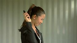 Young asian office worker receiving an angry call on her cell phone, to which she hangs up and throws her phone away - dolly shot.