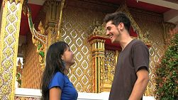 An attractive young Thai girl meets up with her foreign boy friend outside the temple in Bangkok, Thailand.