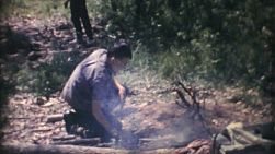 A young Cub Scout makes a fire while camping on a camp out in the summer of 1972.