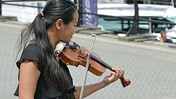 VANCOUVER, BC, CANADA, JUNE 2018: A young female adult Asian girl spends time busking and passionately playing her violin on the streets of Vancouver, BC.