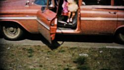 Cute little girls in pretty yellow dresses get out of a classic old car to begin searching for chocolate Easter eggs in the yard in 1961.