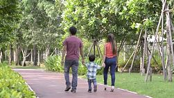 Happy young asian family walking together in a park - dolly tracking shot.