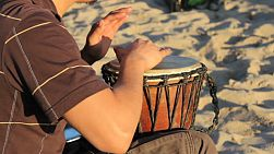 A young man plays his djembe drum on Venice Beach in beautiful Los Angeles, California.