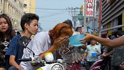 Bangkok, Thailand - April 14, 2014: A young Thai man on a motorbike, stops to try and wash the talcum powder off his face during the annual Songkran Festival, with other revealers splashing him and putting more powder on his face.