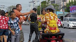Bangkok, Thailand - April 14, 2014: Two young people on a small ATV stopping to get splashed with water and powder on the side of a road, during the Songkran Festival water fights in Bangkok, Thailand.