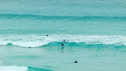 Group of young surfers surfing and body boarding in the beautiful ocean waters near Esperance, Western Australia.