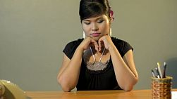 Young asian woman sitting at her retro desk, looking sad and depressed, with her head in her hands - tracking shot.