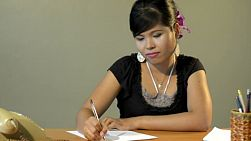 Young asian woman sitting at a retro office desk, writing on paper. tracking shot.