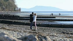 A young romantic couple share a kiss on a beach at Cresent Beach in Vancouver, BC.