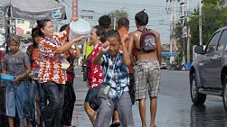 Bangkok, Thailand - April 14, 2014: A Thai boy dancing by the side of the road, with a group of people engaging in a watertight behind him, during the Songkran Festival in Thailand.