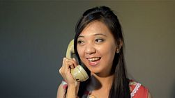 Young asian woman in vintage attire, enjoying a conversation on the telephone - tracking shot.