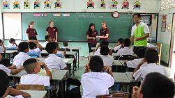 A youth team on a mission trip teaches English to a class of Asian students in Ratchaburi, Thailand.