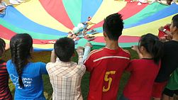 A group of cute Asian kids and a foreign youth missions team have fun playing parachute game in the province of Chiang Rai, Thailand.