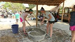 A group of high school students on an overseas missions trip work hard mixing concrete on a construction project in a Karen hill tribe village in Chiang Rai, Thailand.