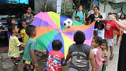 A group of cute Asian kids and a foreign youth missions team have fun playing parachute game in the slums of Bangkok, Thailand.